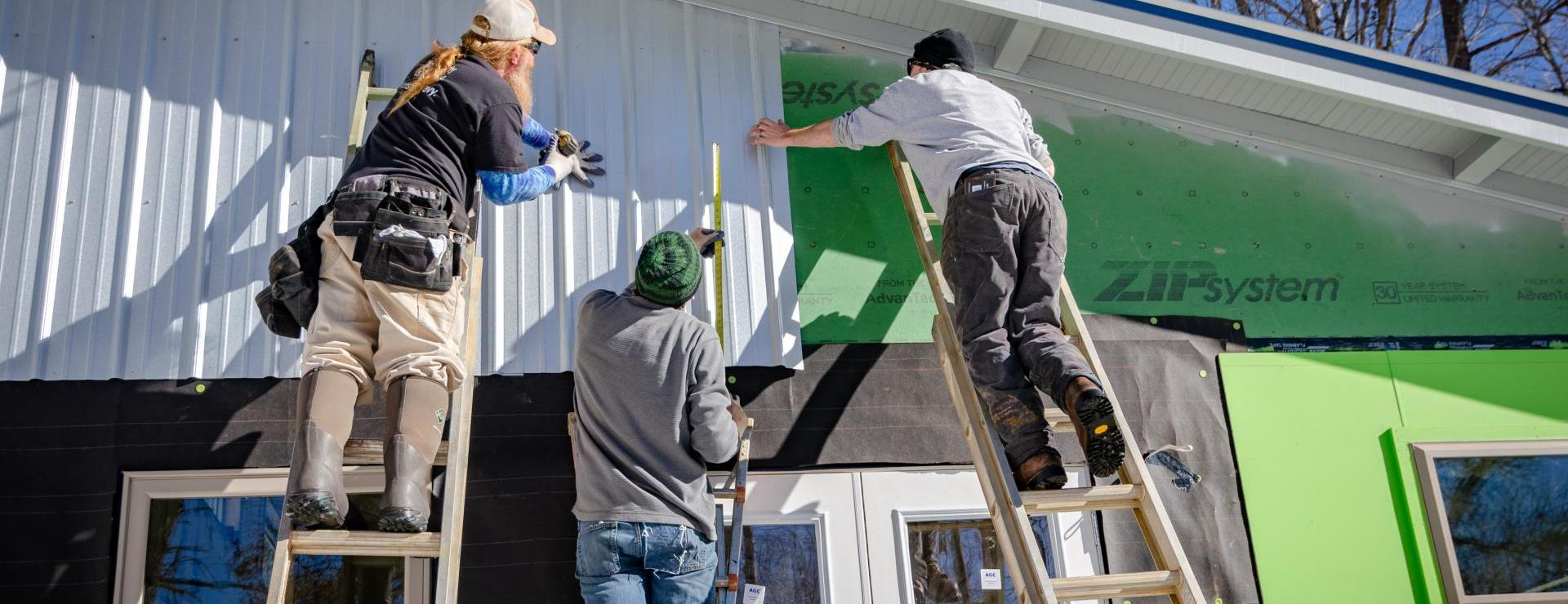 Three people on ladders applying siding to house